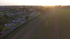 Low aerial flyover approaching suburb adjacent UK countryside at sunset Stock Footage
