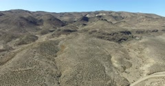 Aerial scene of desertic, dry mountainous landscape. Camera travels slowly at hi Stock Footage