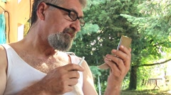 Senior man trimming his facial hair 02 - stock footage