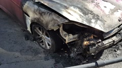Burned car near the road in the city Stock Footage