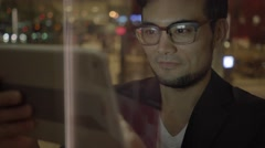 Young man looking at tablet computer searching the web in the city Stock Footage
