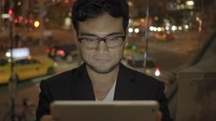 One young man with glasses looking at tablet computer screen in city at night Stock Footage