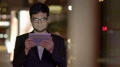 Young asian man standing in the city at night looking at tablet computer screen Stock Footage