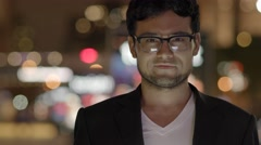 portrait shot of young handsome asian man standing in the city at night - stock footage