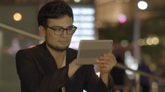 man browsing the web outdoors using modern mobil tablet device - stock footage