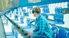 Upset guy in VR glasses sitting on the tribune - stock footage