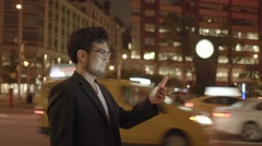 one asian man walking alone on city street at night using tablet computer - stock footage