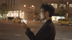 one asian man walking alone through the city at night looking at tablet pc - stock footage