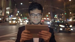Asian man using tablet computer in the city at night Stock Footage