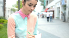 Female student making notes in the city - stock footage
