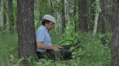 Man working remotely with laptop on the nature Stock Footage