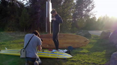 Cameraman films paddle boarder putting on this wetsuit - stock footage