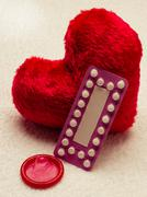 Oral contraceptive pills condom on red heart Stock Photos