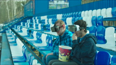 Friends in VR glasses rooting active on the stadium tribune Stock Footage