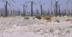 Tilt up from desert to turbines at wind farm 4K - stock footage