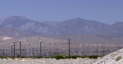 Pan across small and large wind turbines at desert wind farm 4K - stock footage
