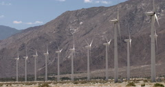 Twelve wind turbines generating energy at desert wind farm 4K - stock footage