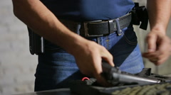 A man preparing to shoot a gun. puts the gun in the holster Stock Footage