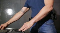 a man preparing to shoot a gun. puts the gun in the holster - stock footage