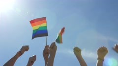 Hands holding rainbow flags against blue sky - stock footage