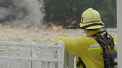 Fireman Watches Blaze Zoom Out Stock Footage