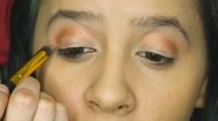 Beautiful girl applying eye shadow in her home makeup studio Stock Footage