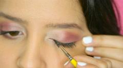 Beautiful girl applying eyeliner in her home studio Stock Footage