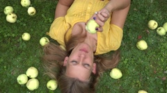 Beautiful smiling young woman lying on grass and bit taste apple fruit. 4K Stock Footage