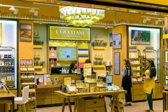 """Saleswoman in a corporate yellow interior of boutique """"L'Occitane"""" - stock photo"""
