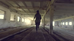 The girl run away from killer through the abandoned building. Slow motion. Stock Footage