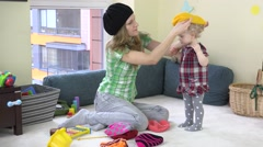 Mother with awesome baby girl measure colorful knitted hats between toys Stock Footage