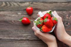 Woman holds a cup full of strawberries in hands. Mug shaped as a heart, symbo Stock Photos