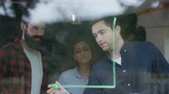 4K Young professional team in business startup drawing graph on window Stock Footage
