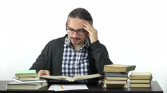 Man sitting at table studying hard. Stock Footage