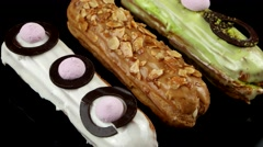 Eclairs with glaze, chocolate, nuts and pistachios no top, closeup, loop Stock Footage