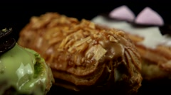 Group of French decorated dessert eclairs, closeup Stock Footage
