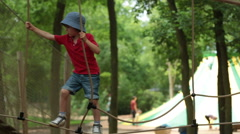 Cute child, boy, climbing in a rope playground structure, springtime Stock Footage
