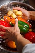 Hands wash potatoes and paprika. Stock Photos