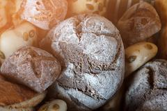Dark brown bread and buns. - stock photo