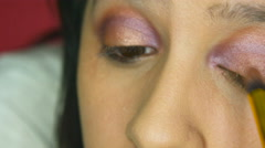 Girl applying dark pink eye shadow in her makeup studio Stock Footage