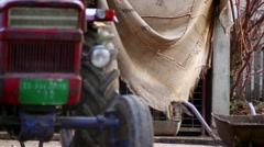 Old tractor in front of a pig house - stock footage