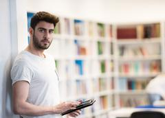student in school library using tablet for research - stock photo