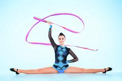 The girl doing gymnastics dance with colored ribbon on a blue background Stock Photos