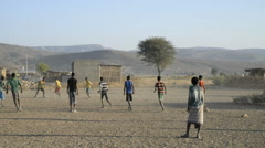 Children play football on a dirt pitch in Abala in Ehtiopia Stock Footage