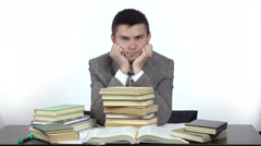 Young tired student is sitting at table surrounded by books. Stock Footage