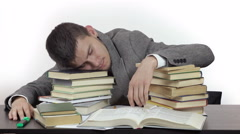 Young tired student is sleeping at table surrounded by books. Stock Footage
