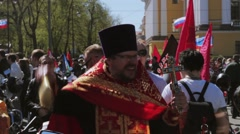 Orthodox priest sprinkles holy water to people. Bikers parade and show. Stock Footage