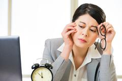 Exhausted asian Businesswoman overtime and overworked - stock photo