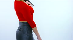 Girl in a black leather skirt and red shirt turn around for the camera - stock footage