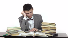 young tired student is reading at table surrounded by books. - stock footage